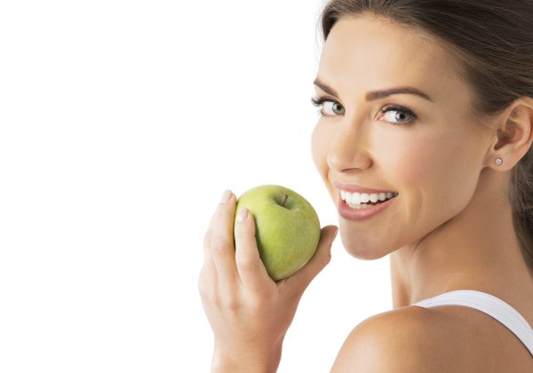 Beautiful woman with healthy white teeth holding green apple isolated on white background